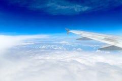 与翼飞机的白色多云和蓝天 库存照片