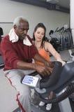 与老人的教练员在健身房的锻炼脚踏车的 库存照片
