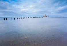 与老军事大厦的波儿地克的岩石海岸从第二次世界大战和木防堤 图库摄影