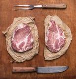 与老刀子和肉叉子土气木背景顶视图关闭的未加工的新鲜的猪肉牛排 免版税库存照片