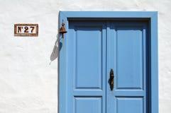 与老响铃的蓝色木门和房子号码签字 免版税库存图片