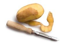 与老土豆削皮器的被剥皮的土豆 免版税图库摄影