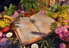 与老开放书、医治草本、花和蜡烛的静物画 免版税库存图片