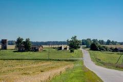 与老房子和路的领域风景 免版税库存照片