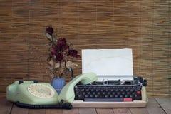 与老打字机电话的静物画有干燥玫瑰色花的 免版税库存照片