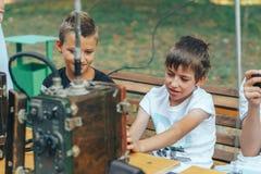与老携带无线电话的孩子 免版税库存图片