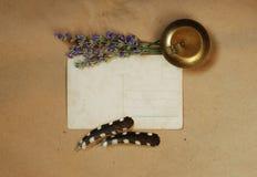 与老明信片、淡紫色鼻烟壶、花束和羽毛的葡萄酒背景 免版税库存照片