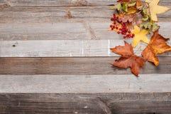 与老木桌和黄色下落的叶子的背景纹理 库存照片