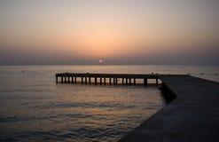 与老木码头的背景在日落的海 免版税库存图片