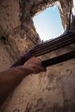 与老梯子的脏的内部,在末端的蓝天和手 免版税图库摄影