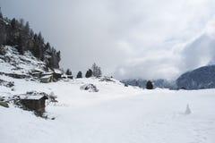 与老棚子和一个小的雪人的高山风景 免版税库存图片