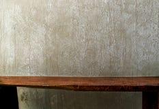 与老水泥墙壁的特写镜头木长凳 免版税库存照片