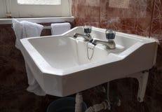 与老瓦片的经典白色水槽在有毛巾的一个卫生间里 库存图片