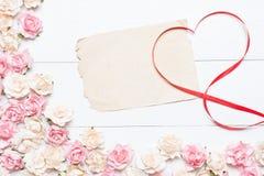 与老白纸板料和桃红色玫瑰的红色丝带心脏标志 库存图片