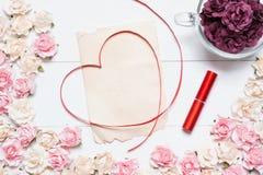 与老白纸板料和玻璃杯子的红色丝带心脏标志 库存图片