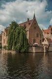 与老砖瓦房的叶茂盛树在运河` s边缘在一个晴天在布鲁日 免版税库存图片