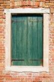 与老绿色木快门在砖墙太阳日,威尼斯的窗口 库存照片