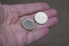 与老设计的新的英国1英镑硬币在手中 免版税图库摄影
