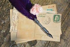 与老邮票的老空白的葡萄酒明信片在与桃红色玫瑰和鸟嘴的老木头 免版税库存图片