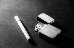 与老金属打火机的香烟 免版税库存照片