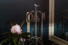 与老首饰、牡丹花和镜子的减速火箭的室内设计 免版税图库摄影