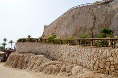 与老,古老黄色鹅卵石和楼梯栏杆一个石墙的美丽的岩石反对蓝天和棕榈树在tropi 库存图片