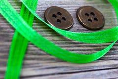 与老绿色磁带和两个葡萄酒按钮的静物画 免版税图库摄影