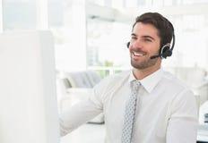 与耳机互动的微笑的商人 免版税库存图片