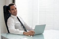 与耳机和便携式计算机的商人 免版税图库摄影