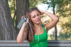 与耳机和拿着智能手机的女孩听的音乐 免版税库存图片