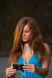 与耳机和拿着智能手机的女孩听的音乐 免版税库存照片