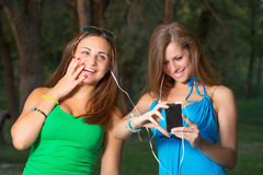 与耳机和拿着智能手机的女孩听的音乐 免版税图库摄影