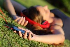 与耳机和拿着说谎在草的一个巧妙的电话的女孩听的音乐 免版税库存照片