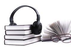 与耳机和眼镜的书 音频书概念 免版税库存照片