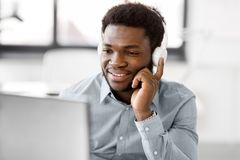 与耳机和计算机的商人在办公室 免版税图库摄影