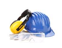 与耳机和风镜的蓝色安全帽 库存照片