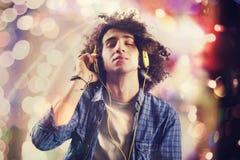 年轻与耳机的人听的音乐 免版税库存照片