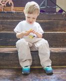与耳机的儿童游戏,听到从您的电话的音乐 库存图片