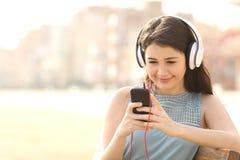 与耳机的女孩听的音乐从一个巧妙的电话 库存图片