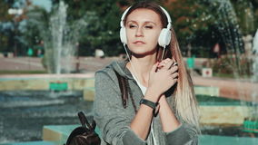 与耳机的妇女听的无线音乐从在街道的一个巧妙的电话 影视素材