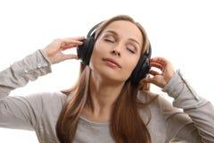 与耳机的少妇听的音乐 免版税库存照片