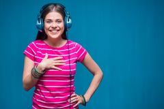 与耳机的微笑的女孩听的音乐 图库摄影
