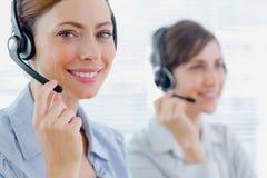 与耳机的微笑的电话中心代理在工作 库存图片