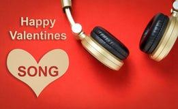 与耳机的愉快的华伦泰爱情歌曲在红色 免版税库存照片