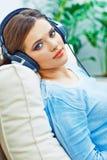 与耳机的愉快的微笑的妇女听的音乐 图库摄影