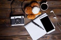 与耳机的照相机用新月形面包和咖啡在笔记本旁边 库存图片