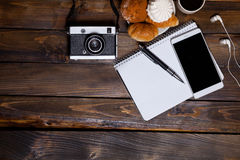 与耳机的照相机用新月形面包和咖啡在笔记本旁边 免版税库存照片