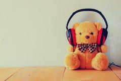 与耳机的玩具熊在木桌 免版税库存照片