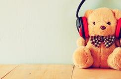 与耳机的玩具熊在木桌 库存图片