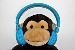 与耳机的玩具猴子 免版税库存照片